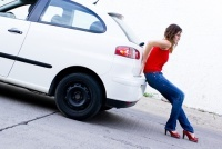 woman pushing car